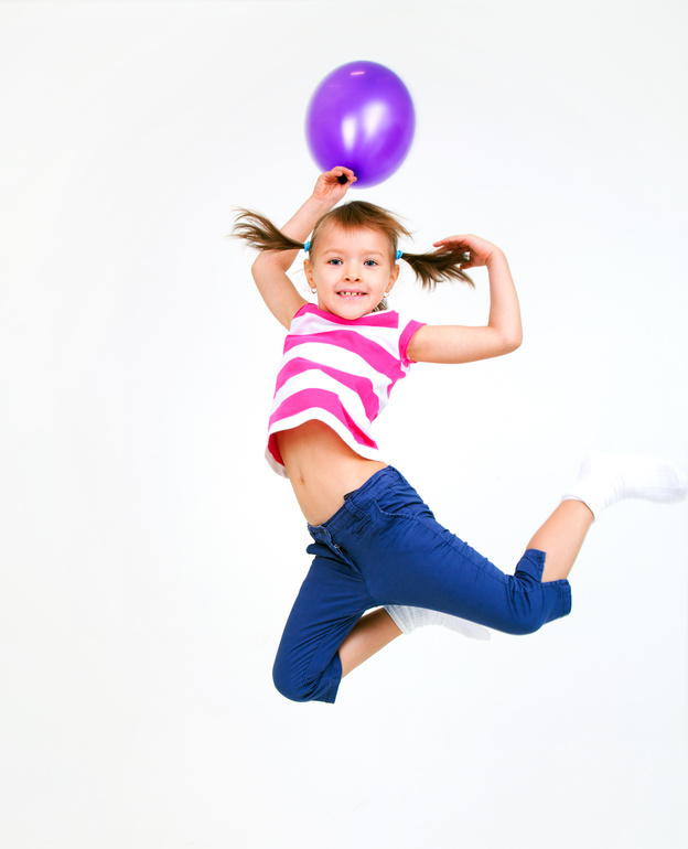Portrait of cute little girl jumping with violet balloons